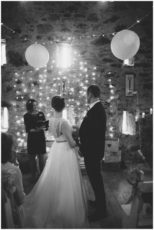 A black and white image of a bride and groom during their ceremony looking at their celebrant