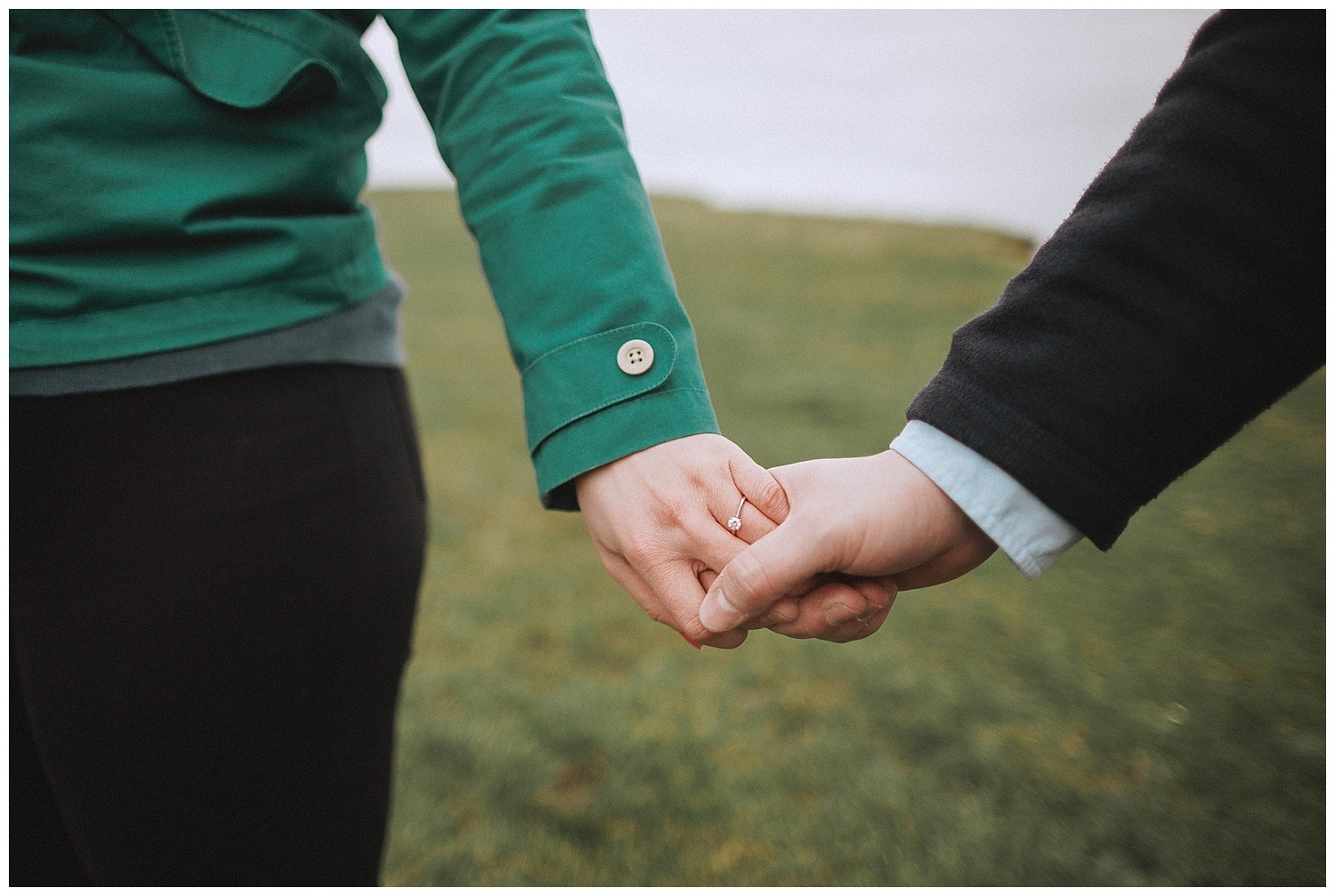 close up of an engaged couple holding hands