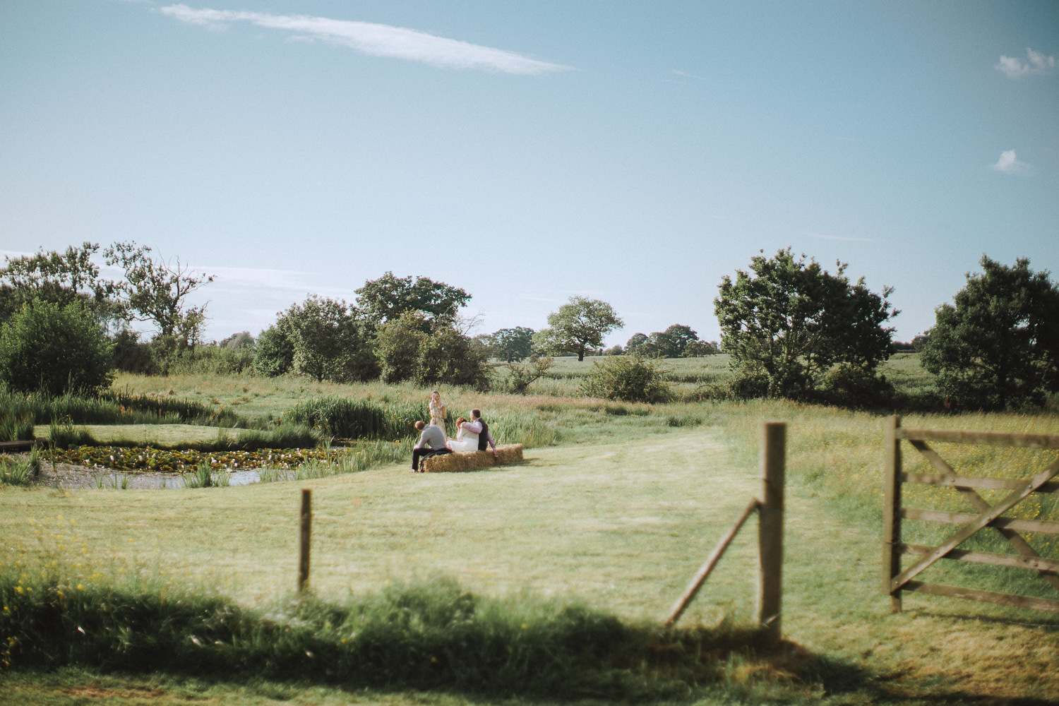 some wedding guests sat on a hay-bail near a pond