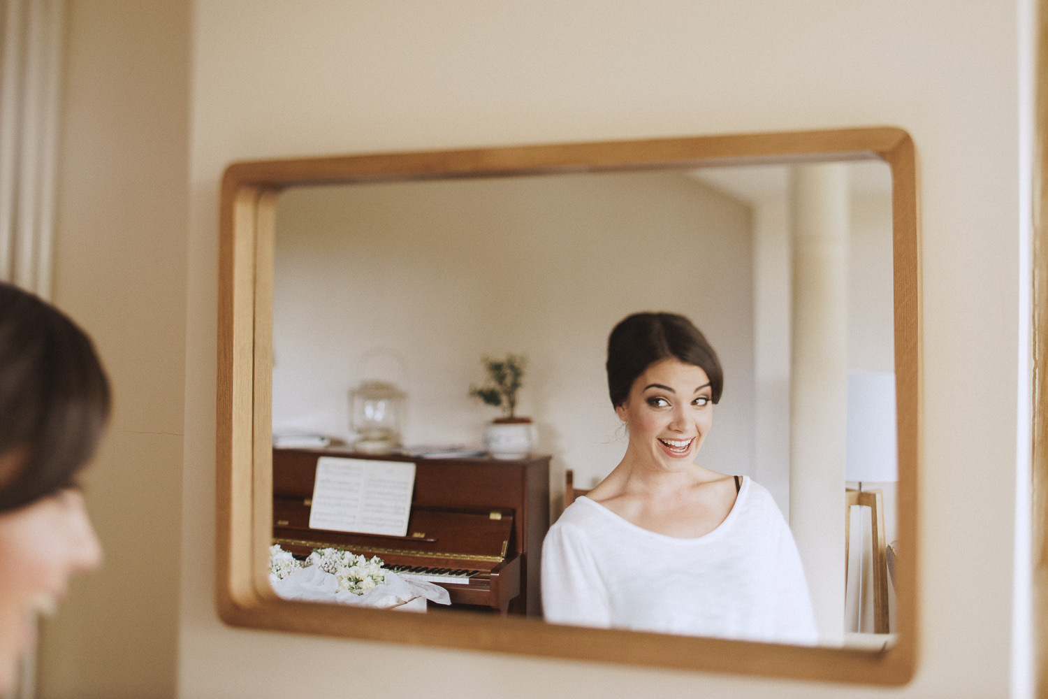 A smiling bride in front of the mirror