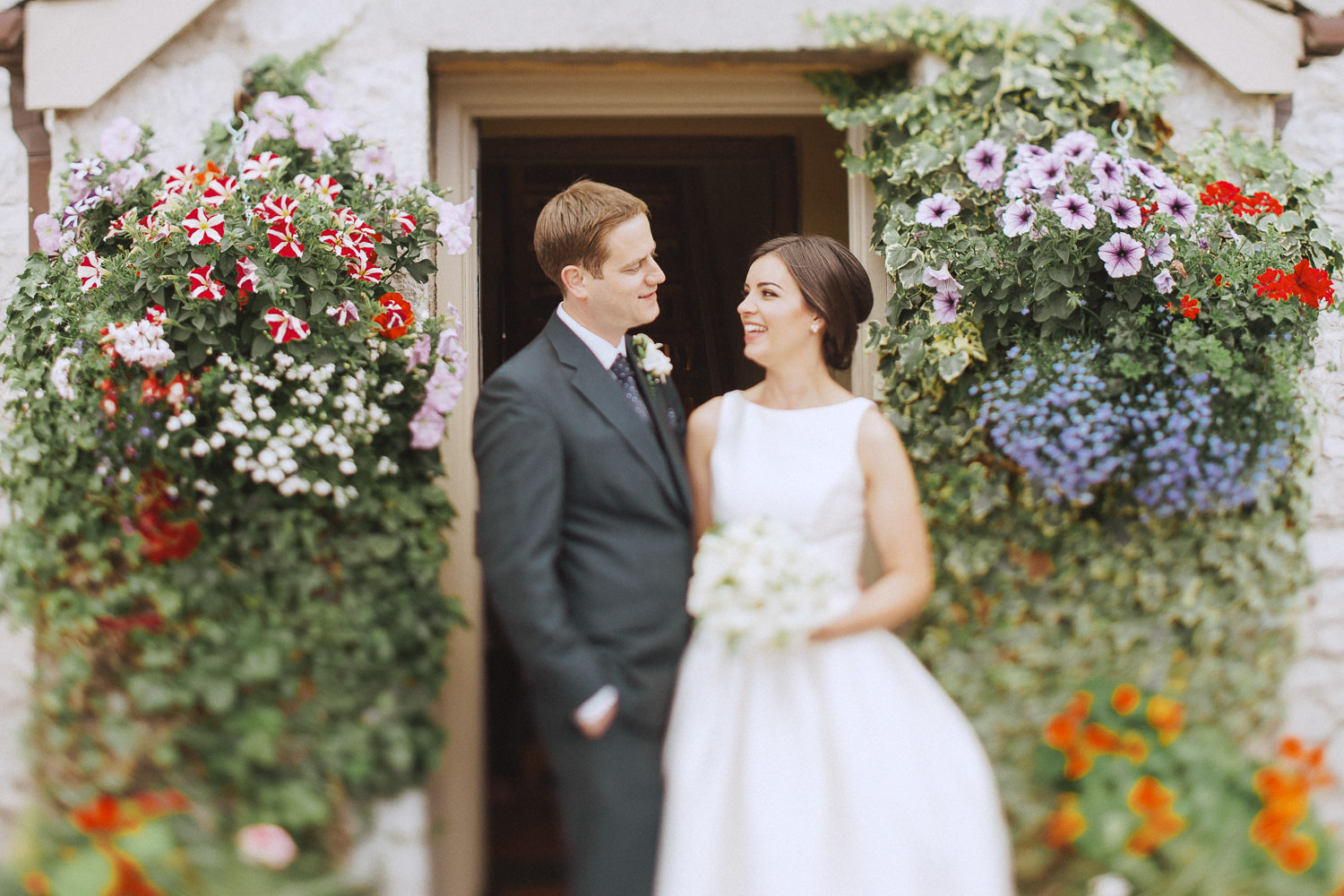 a bride and groom standing in a doorway full of flowers
