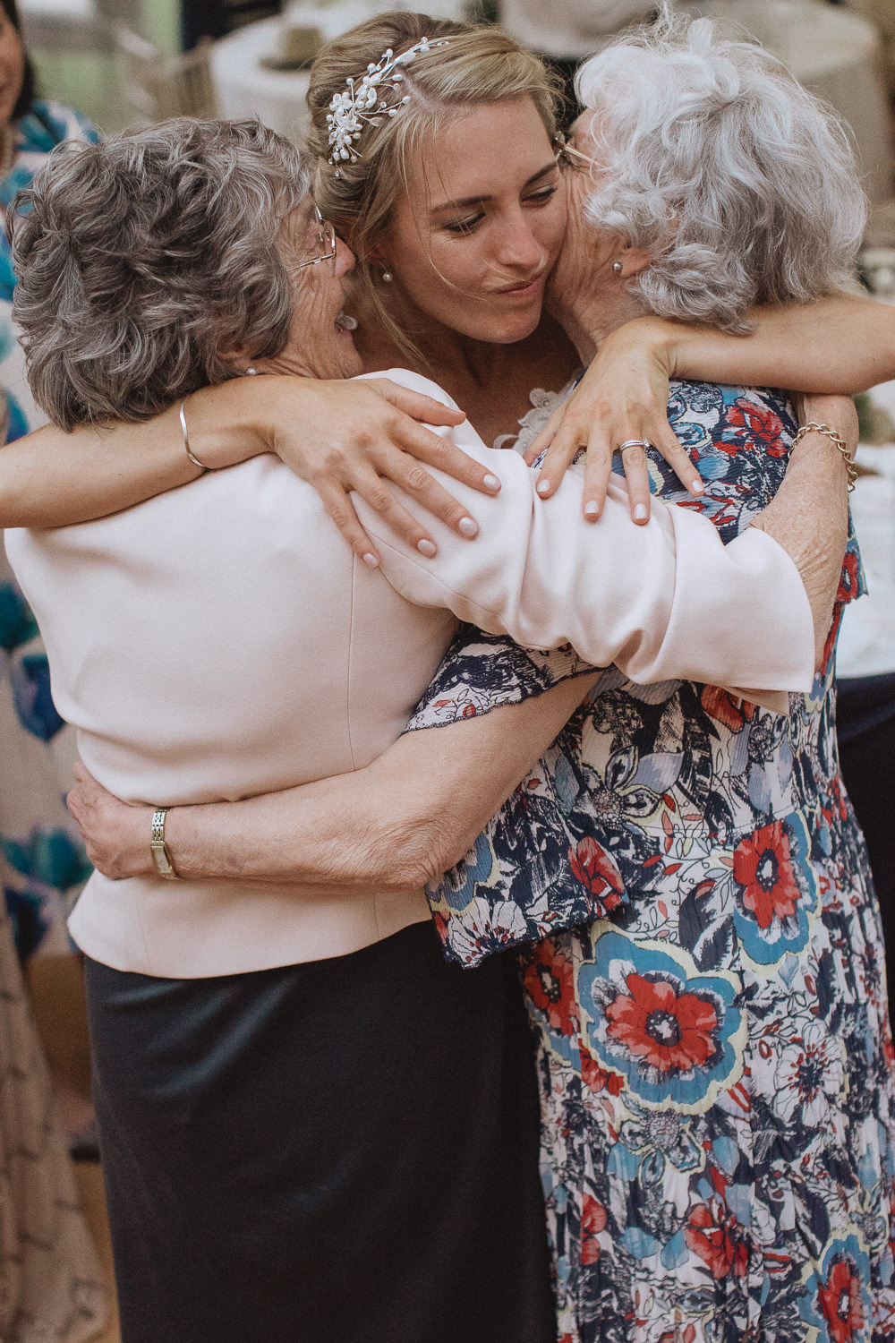 bride hugging her two grandmothers
