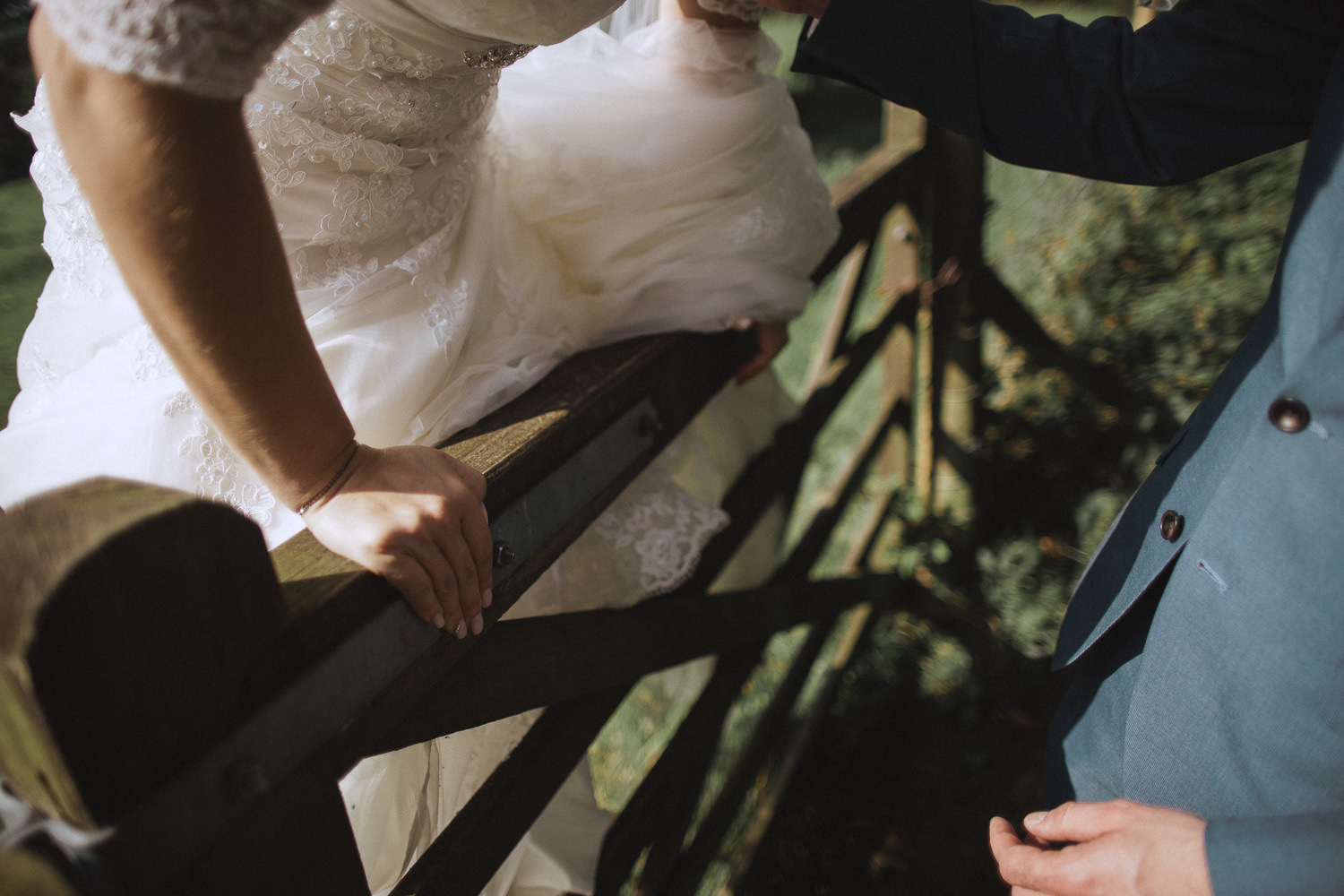 Bride is climbing over a fence