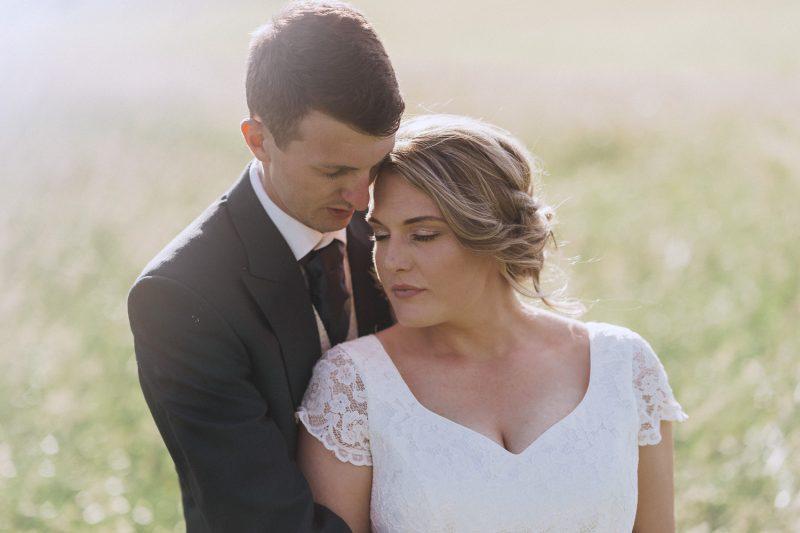 married couple in a hay field