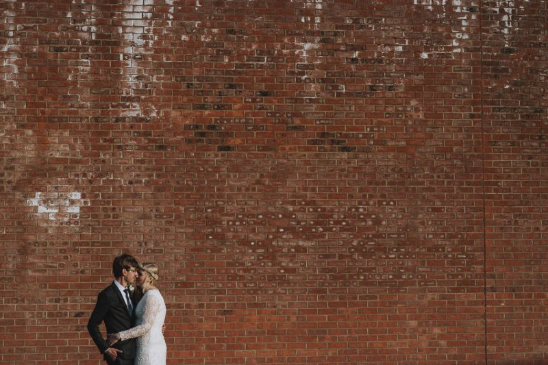 Negative space photograph of a bride and groom in front of a brick wall