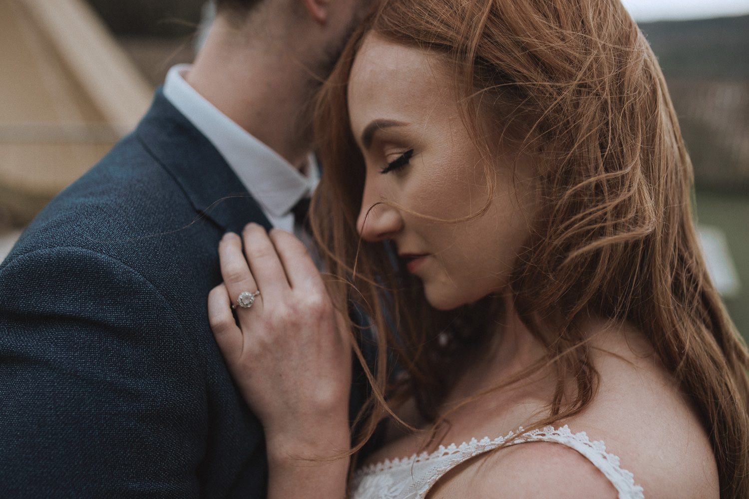 redhead bride holding on close to her groom