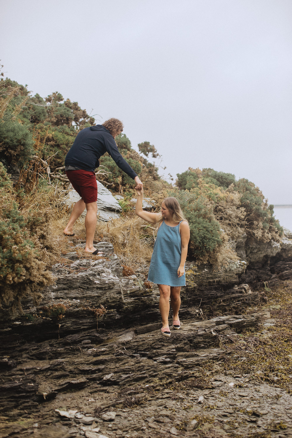 holding hands and climbing rocks at Trearddur Bay, Anglesey, North Wales
