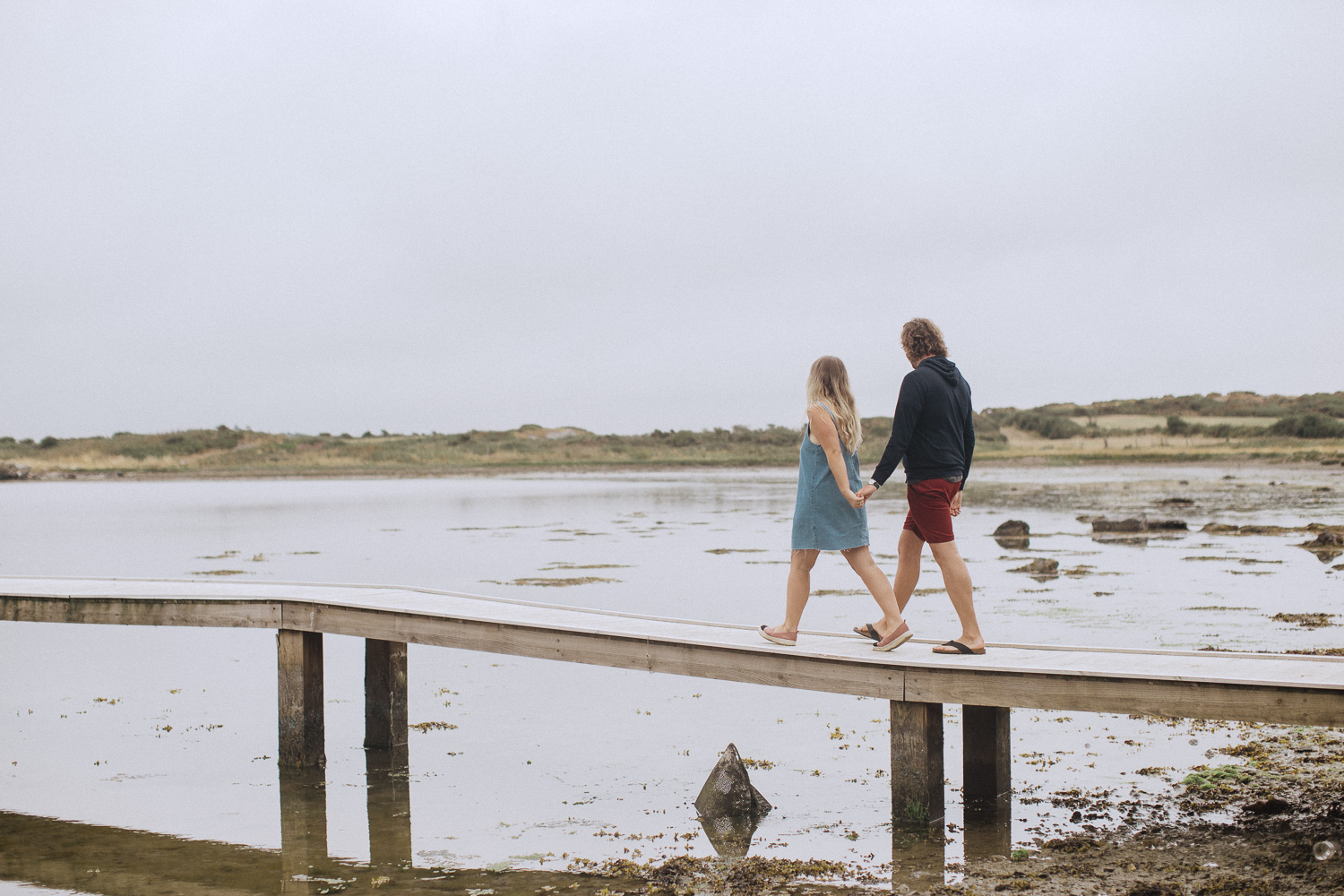a couple holding hands and walking along a jetty at Trearddur Bat, Anglesey, North Wales