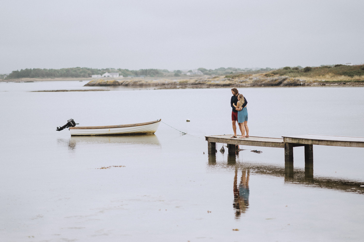 a couple hugging at the end of a jetty