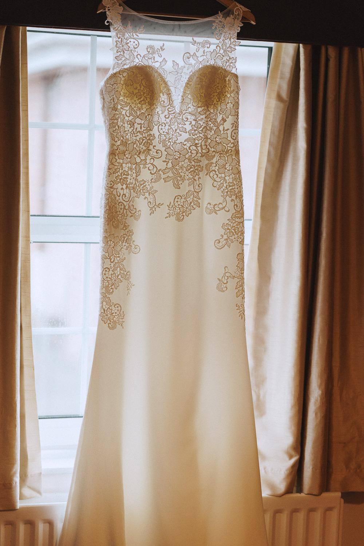 wedding dress hung up on a window