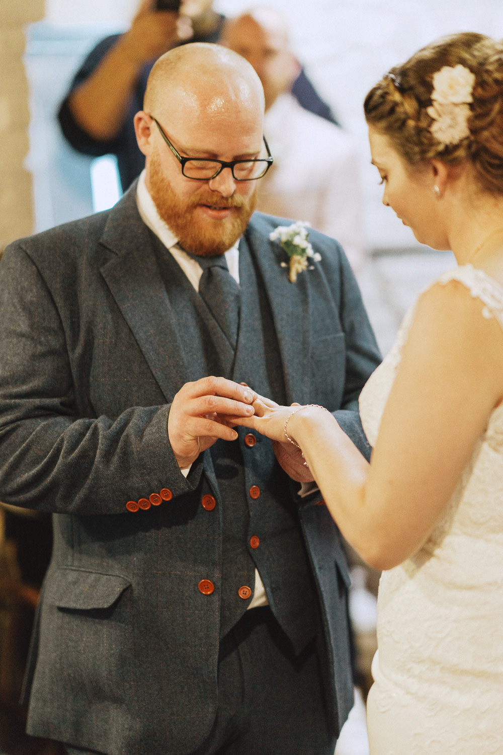 bearded groom putting the ring on his bride