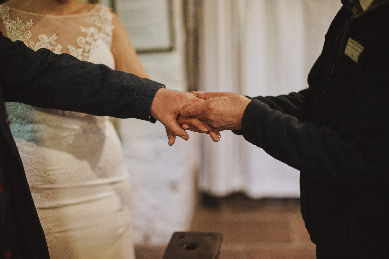 bride, groom and celebrant holding hands at gretna green