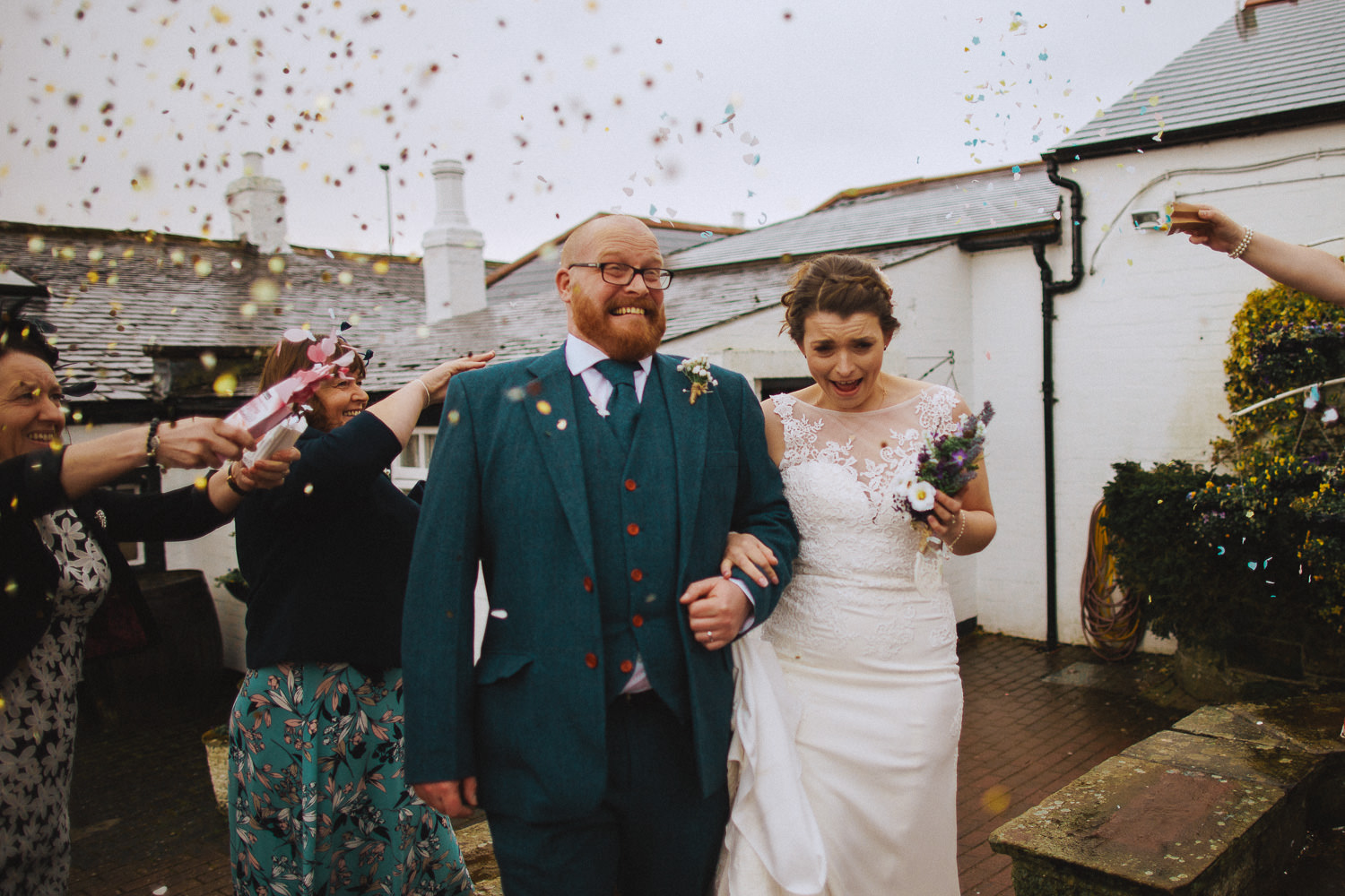 bride and groom pulling faces as they have confetti thrown at them