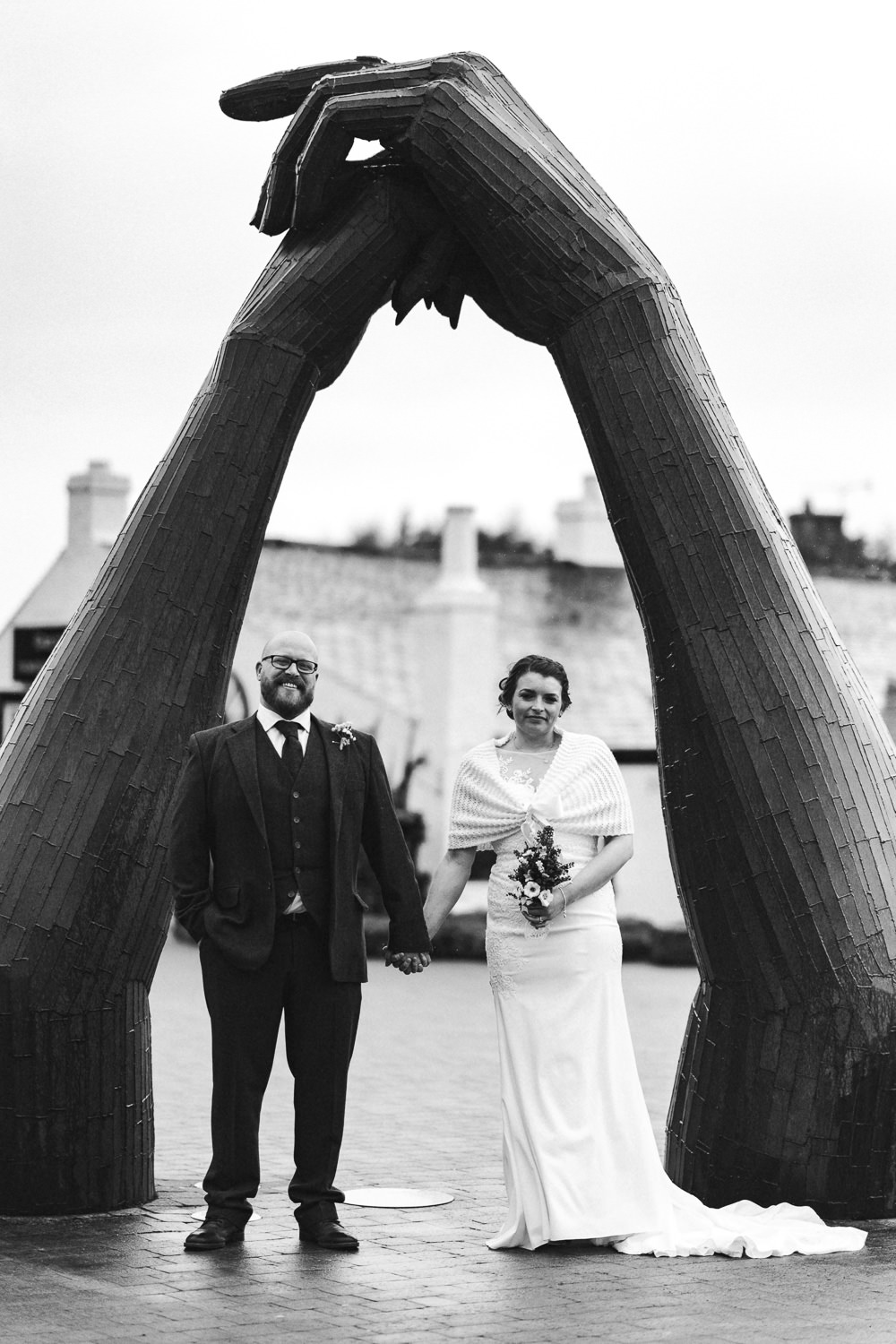 bride and groom under a statue of hands holding