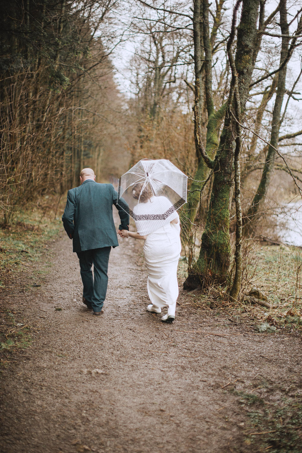 bride and groom walking in a country path with wellies and an umbrella