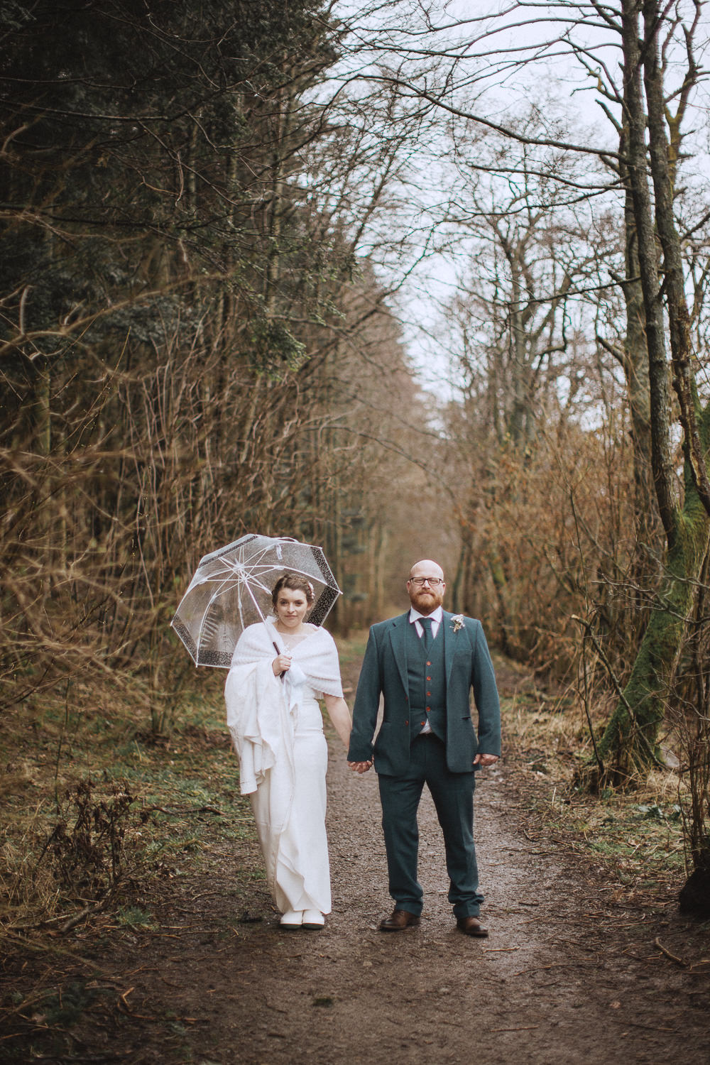 bride and groom standing together in the country while the bride holds an umbrella