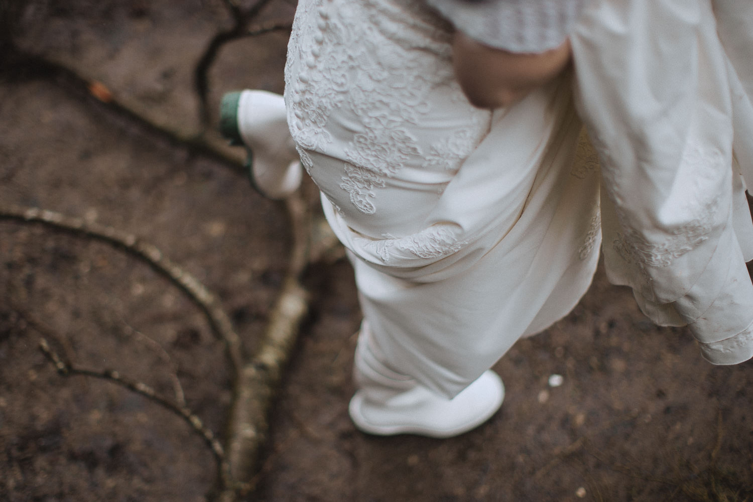 close up of a bride walking over a branch