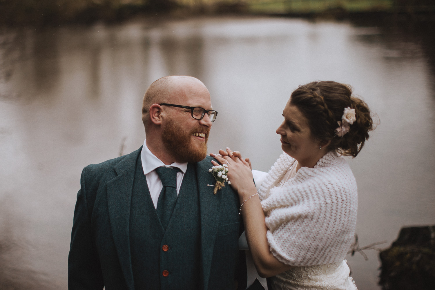 bride and groom laughing in front of a lake