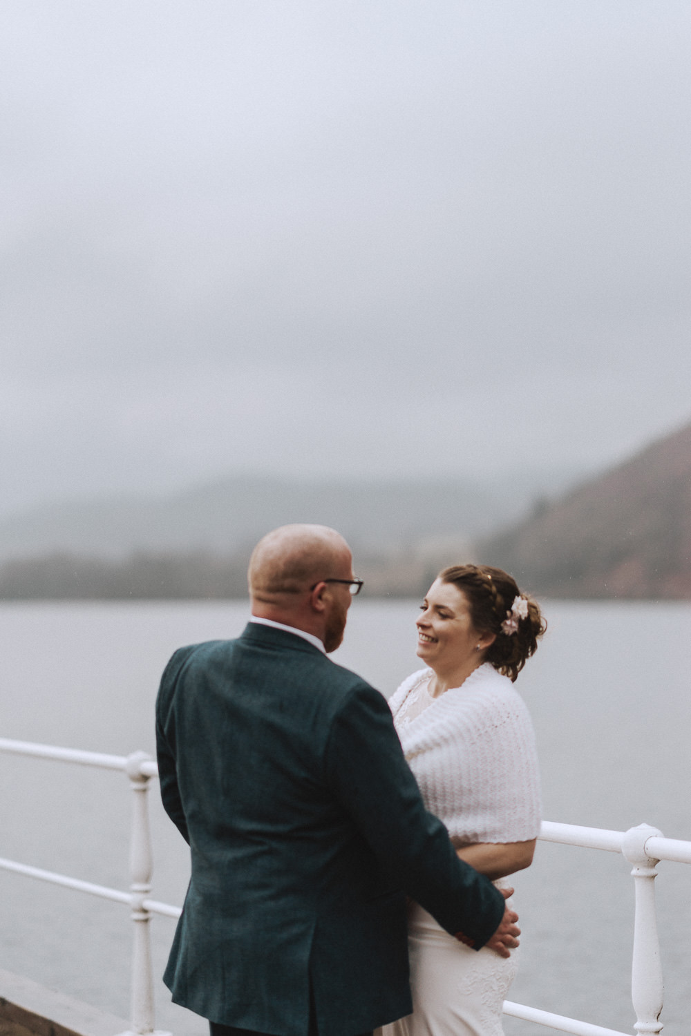 bride and groom on a jetty in the lake district
