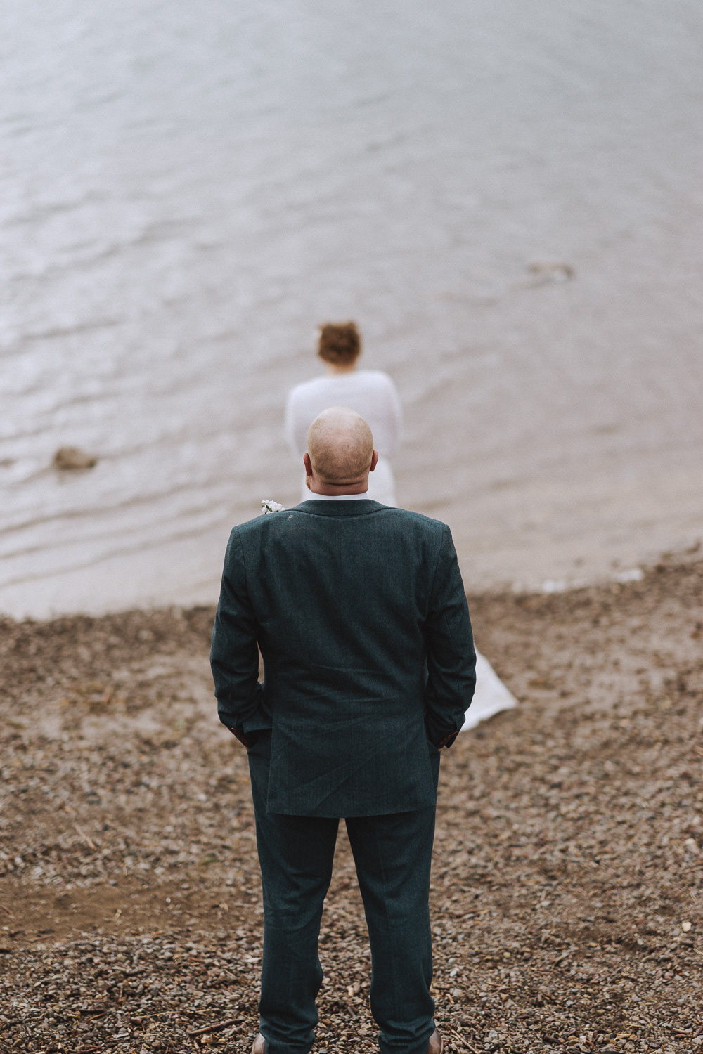 back of a groom looking at his wife at a lakeside