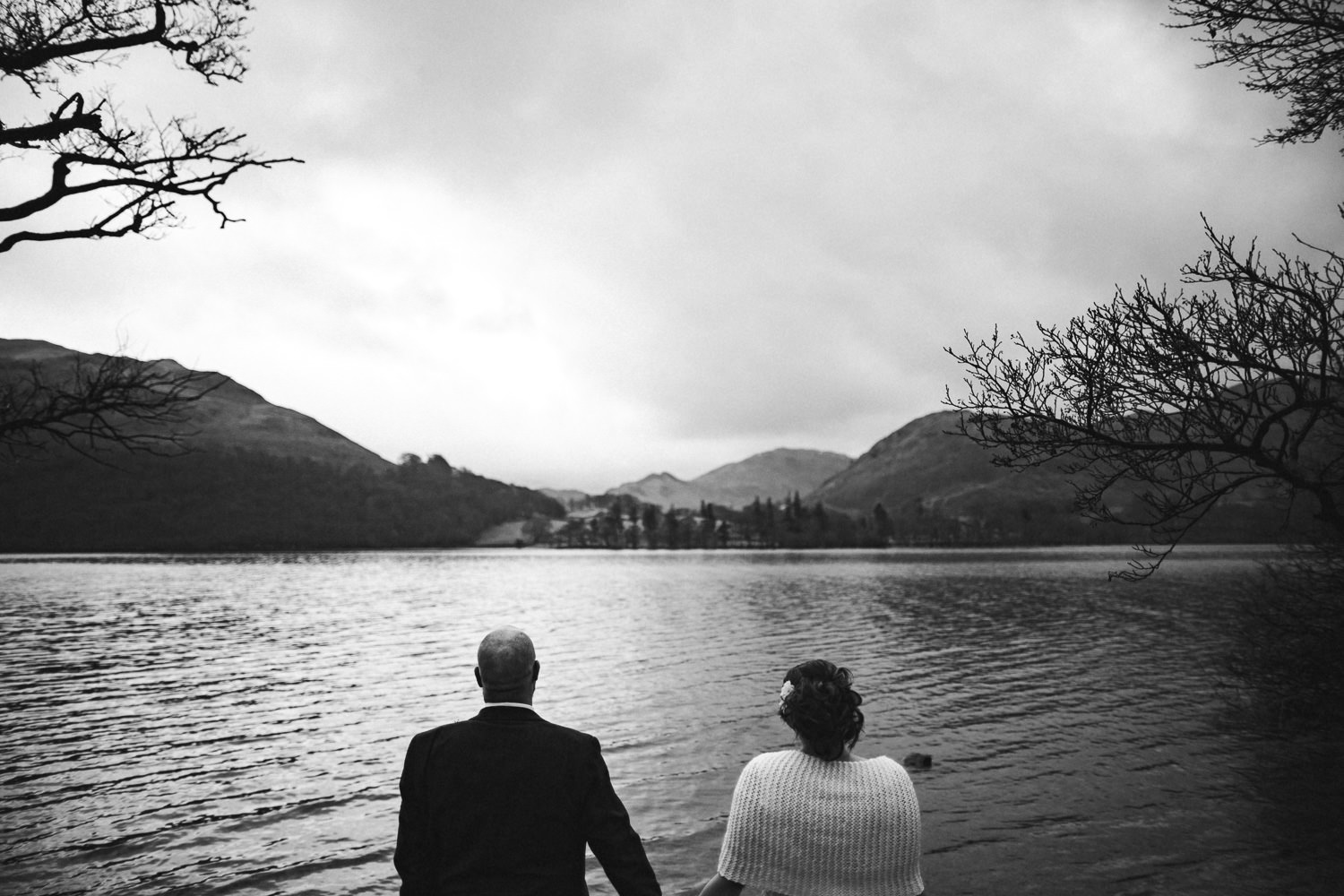 bride and groom looking at the lake district