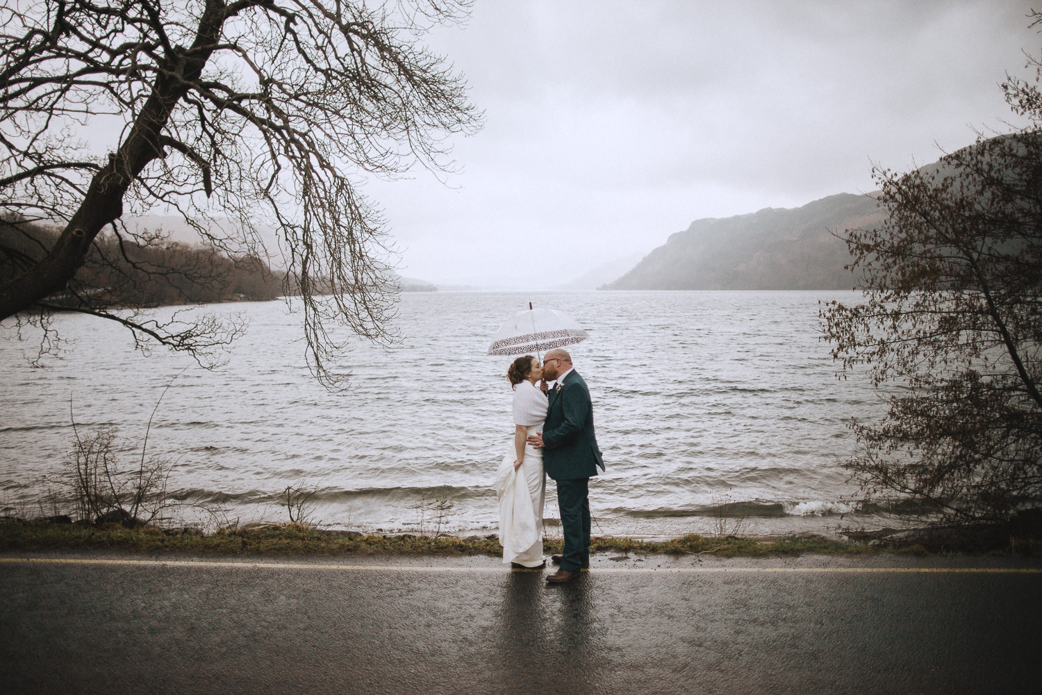 bride and groom under an umbrella by ullswater lake