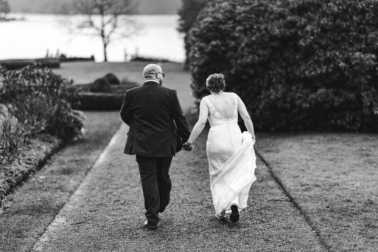 a bride and groom walk towards the lake at inn on the lake