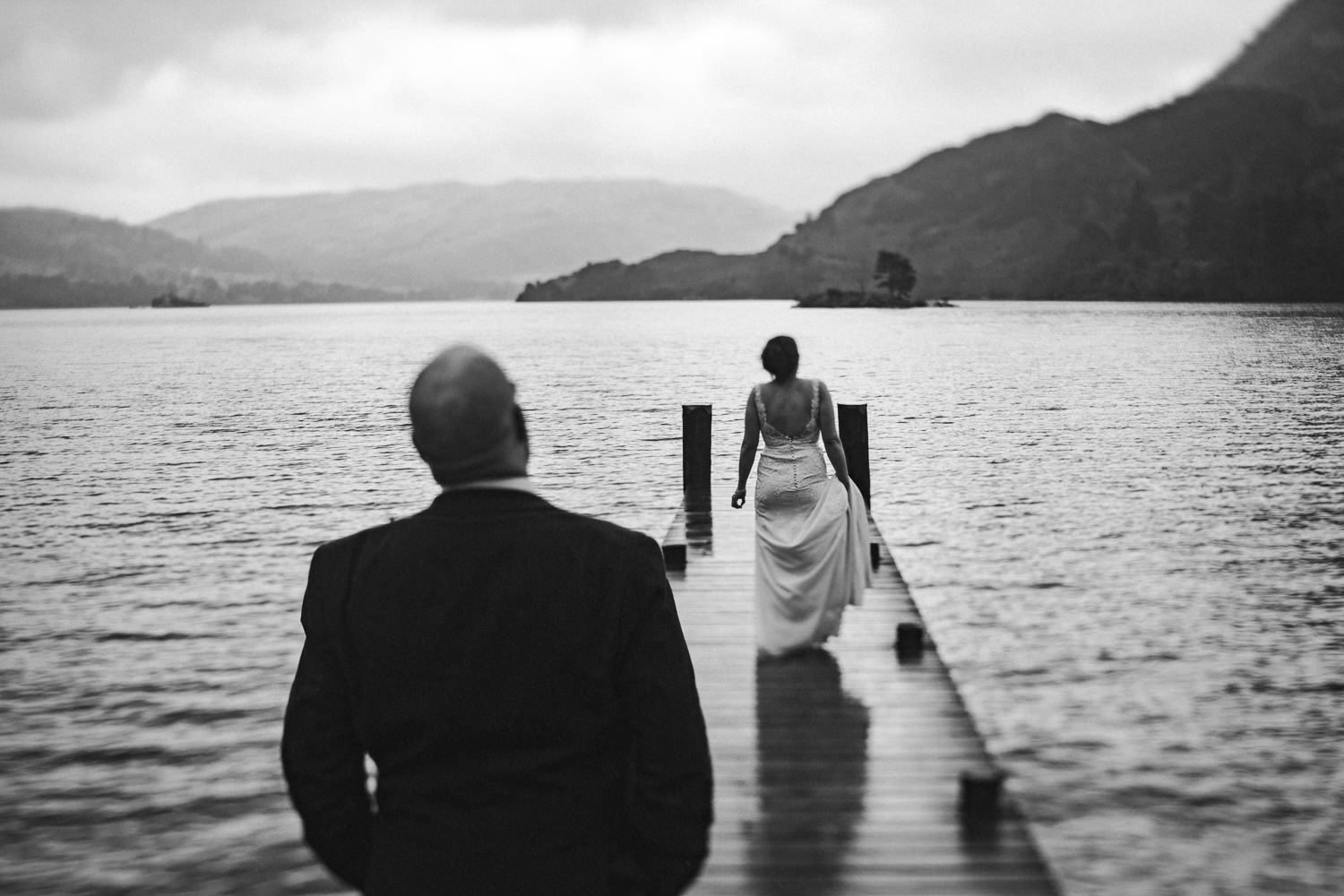 a groom looks at his bride on a jetty at inn on the lake
