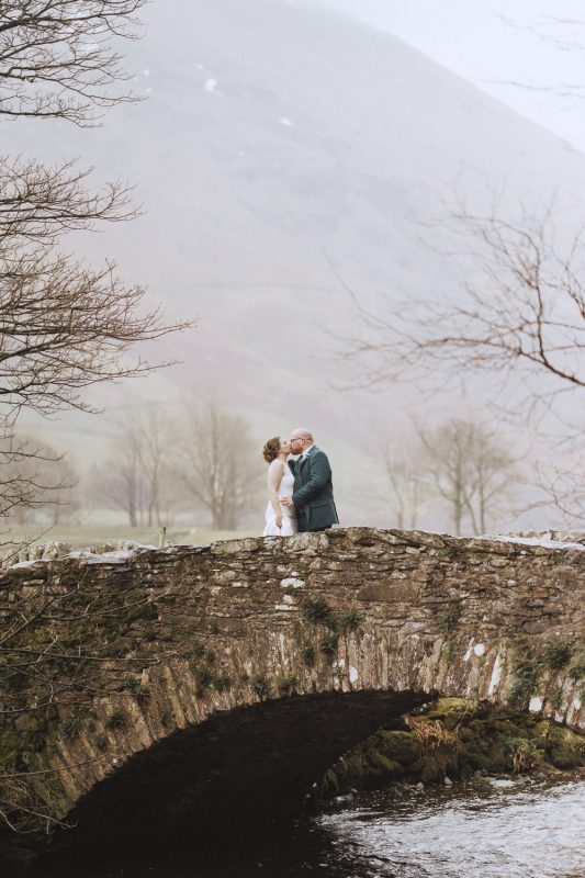 bride and groom standing on a bride in the lake district