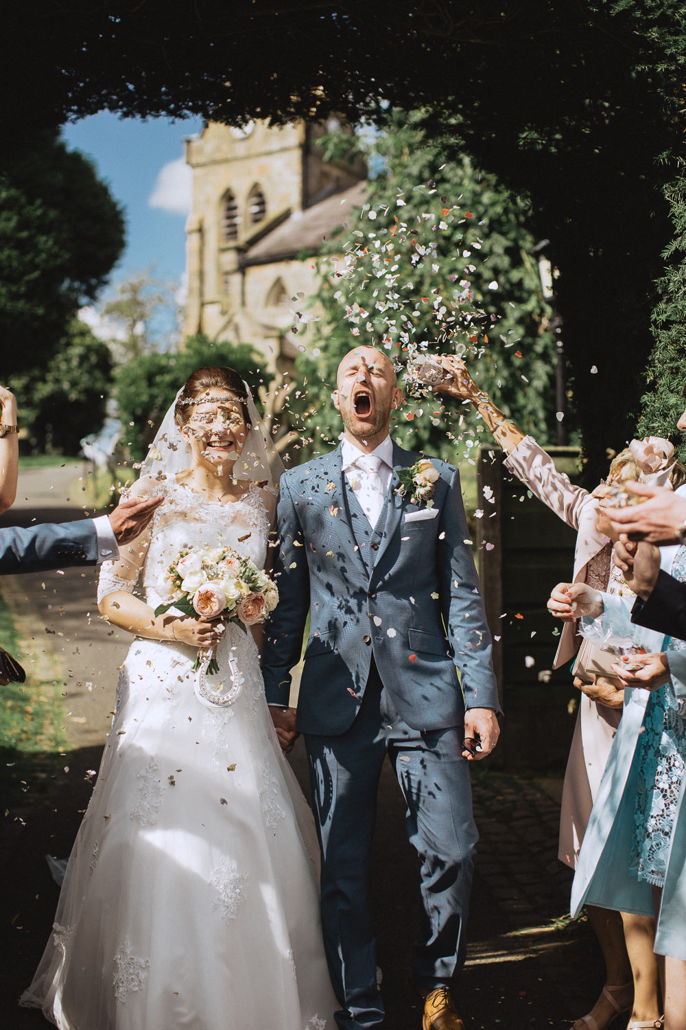Scout Hut Wedding from Fox & Bear Photography - confetti run with the groom trying to catch confetti with his mouth