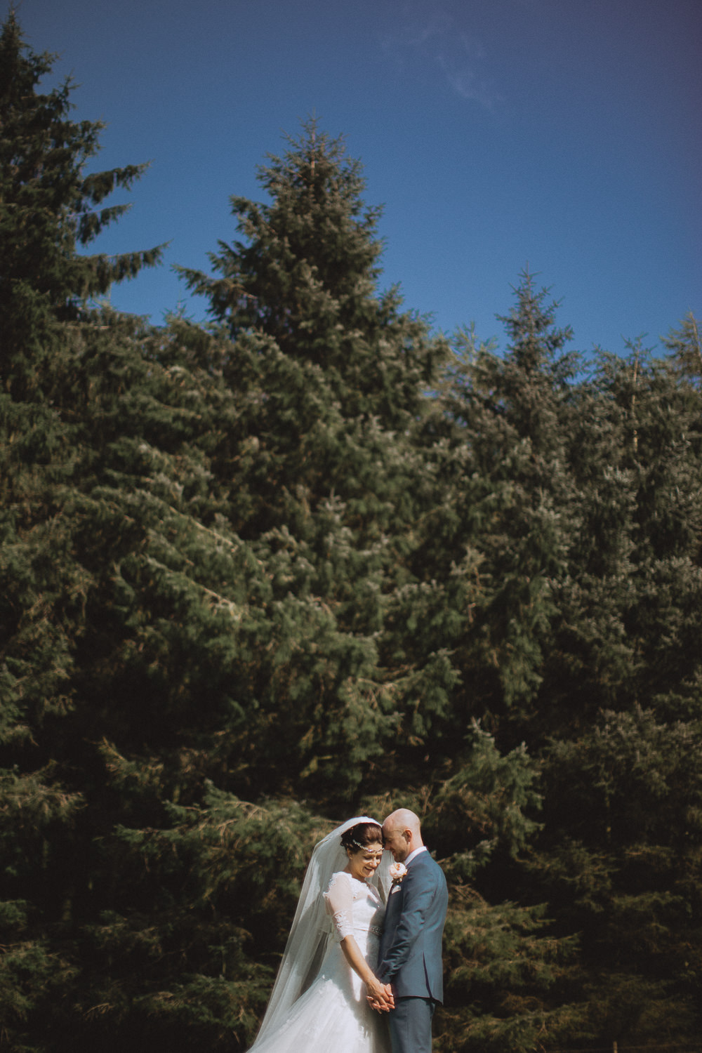 Scout Hut Wedding from Fox & Bear Photography - bride and groom in an embrace in front of a forest