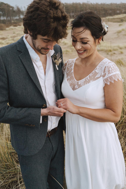 Bride and groom on Newborough Beach looking at their rings