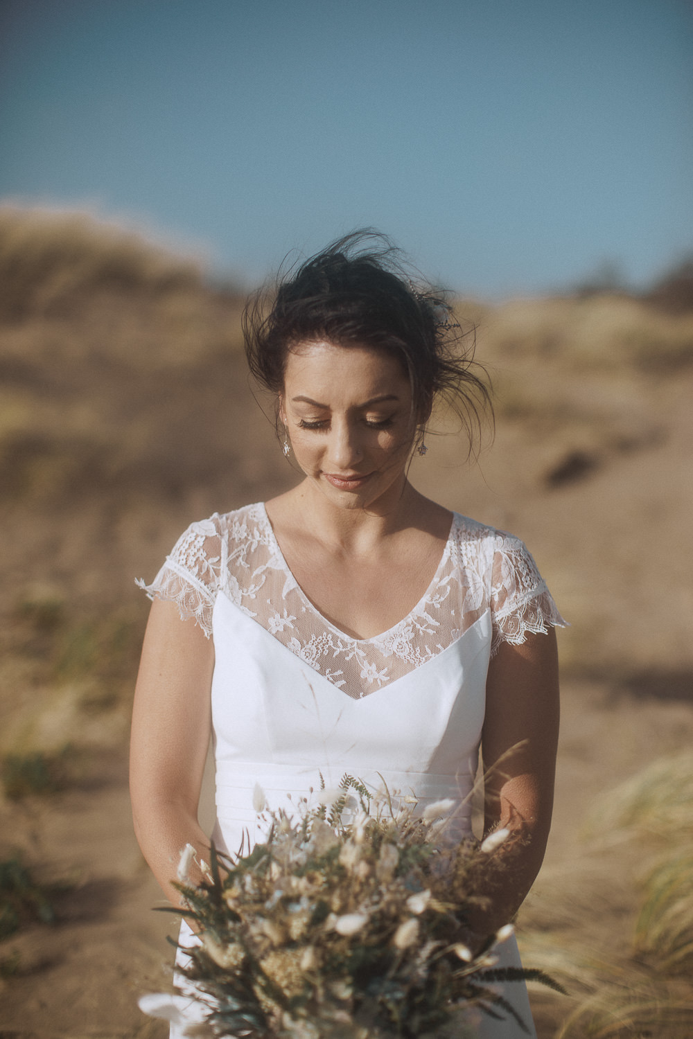 Bride looking at her dried flower bouquet