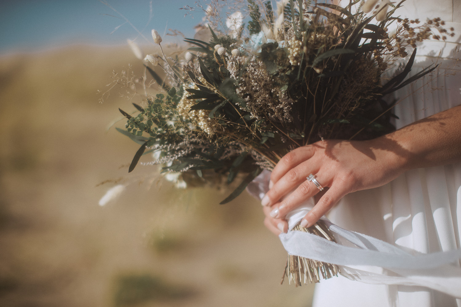 A bride holding her dried flower bouquet on Newborough Beach, Anglesey, Wales