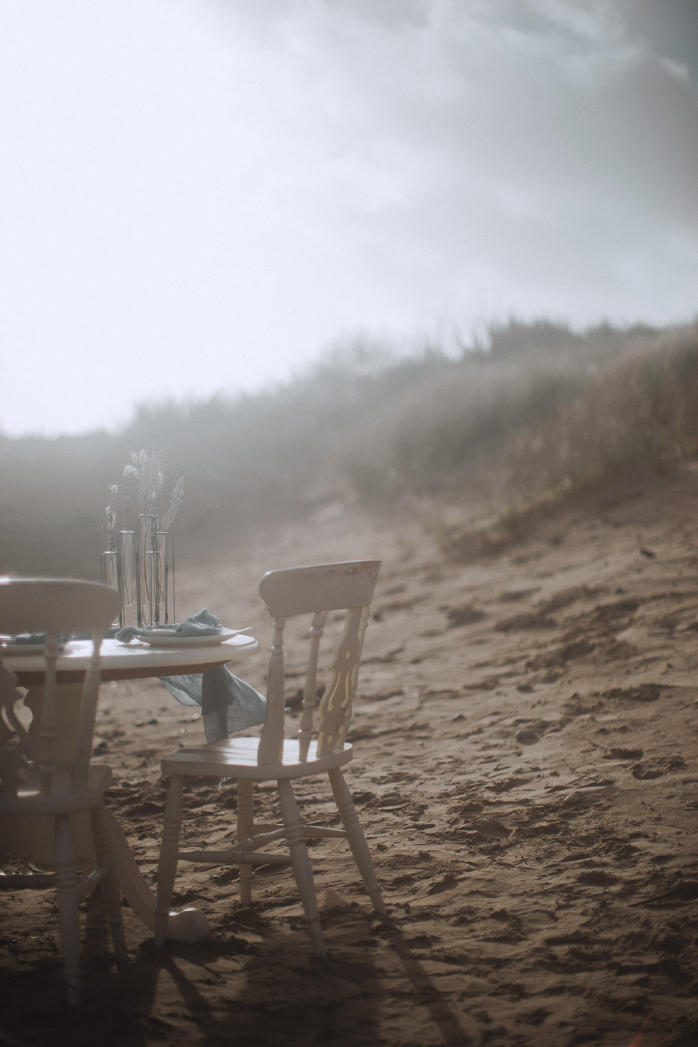 Hazy sandy wedding table set up at Newborough Beach, Anglesey, Wales