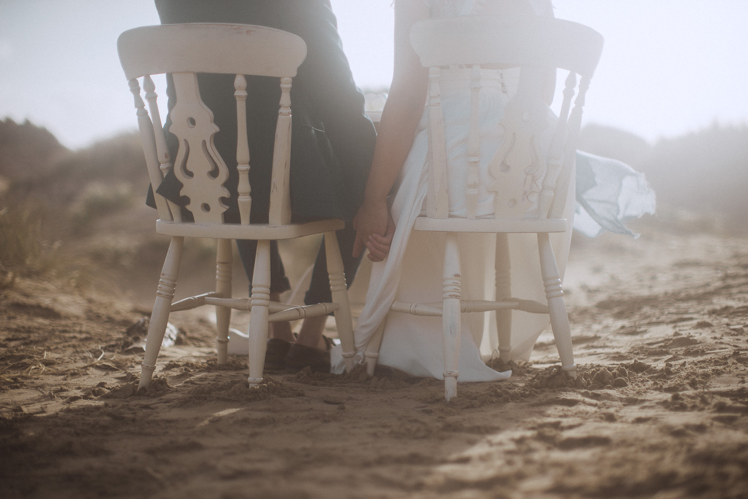 Bride and Groom holding hands at their beachside dining table Newborough Beach, Anglesey, Wales