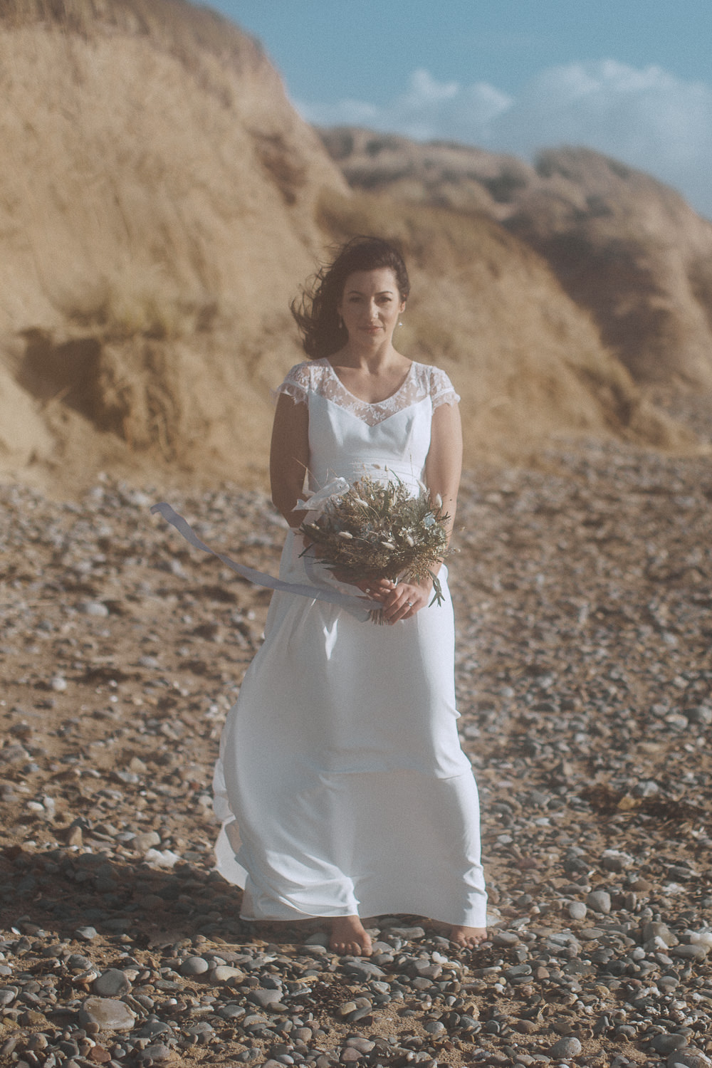 Bride and her dried flower bouquet Newborough Beach, Anglesey, Wales