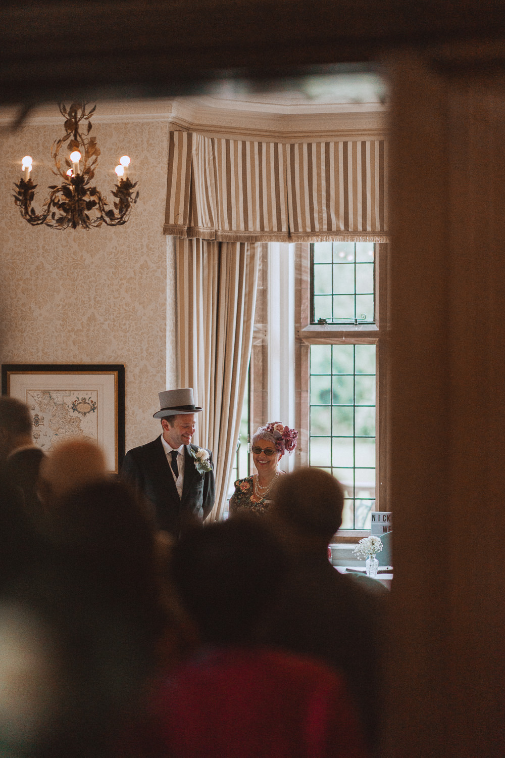 Best man in a top hat chatting with the celebrant at Inglewood Manor, Cheshire