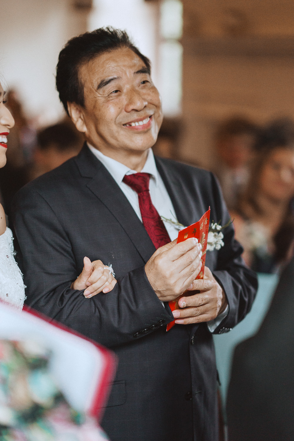 Chinese father in law handing a red envelope at a wedding in Inglewood Manor, Cheshire