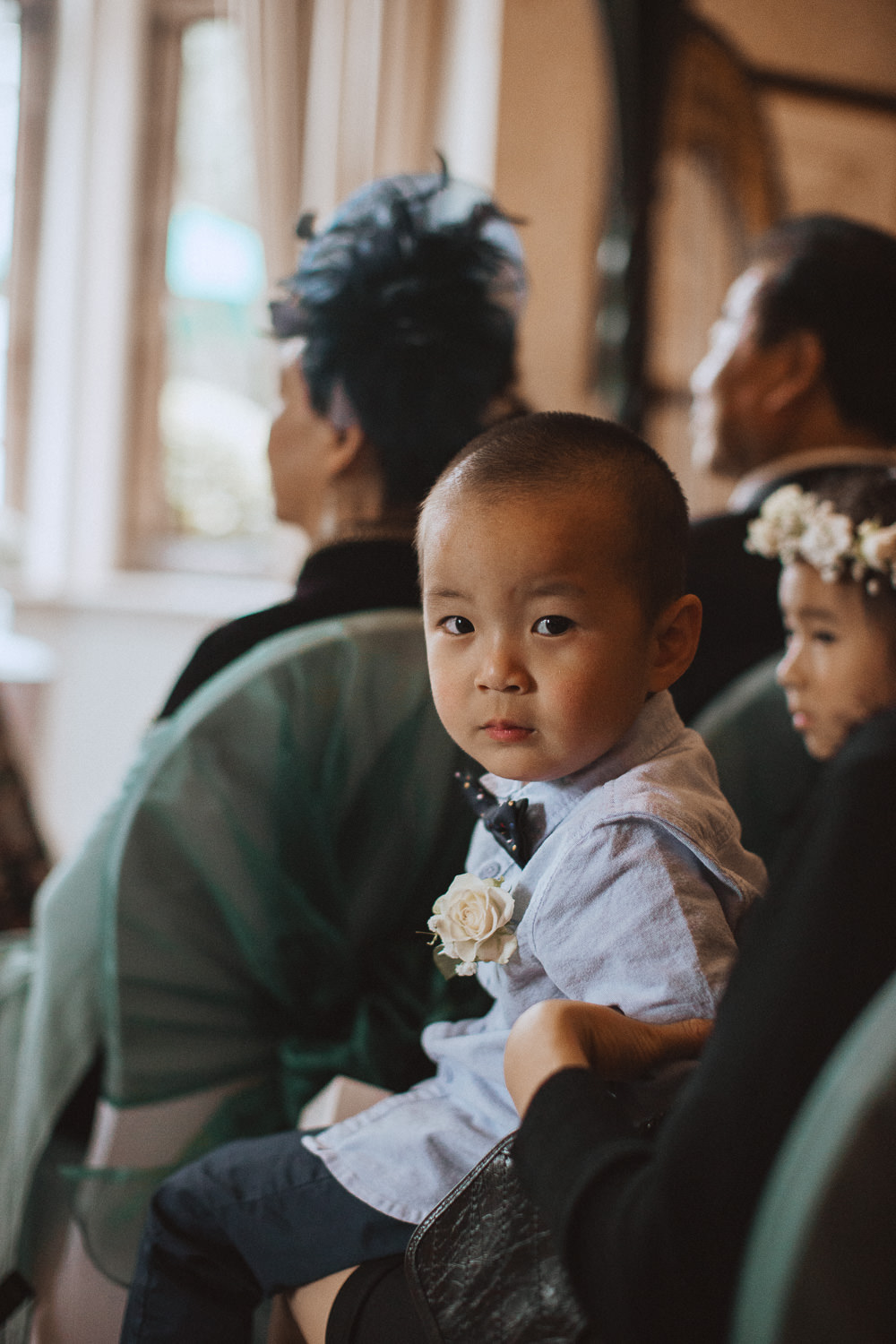 Chinese boy looking at the camera during a ceremony at Inglewood Manor, Cheshire