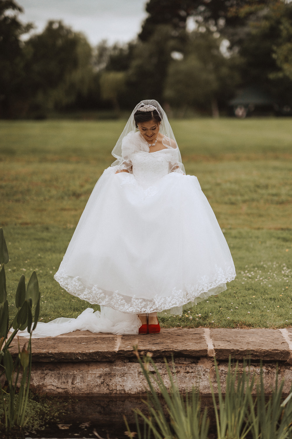 Bride listing her dress to show off her red shoes at Inglewood Manor, Cheshire