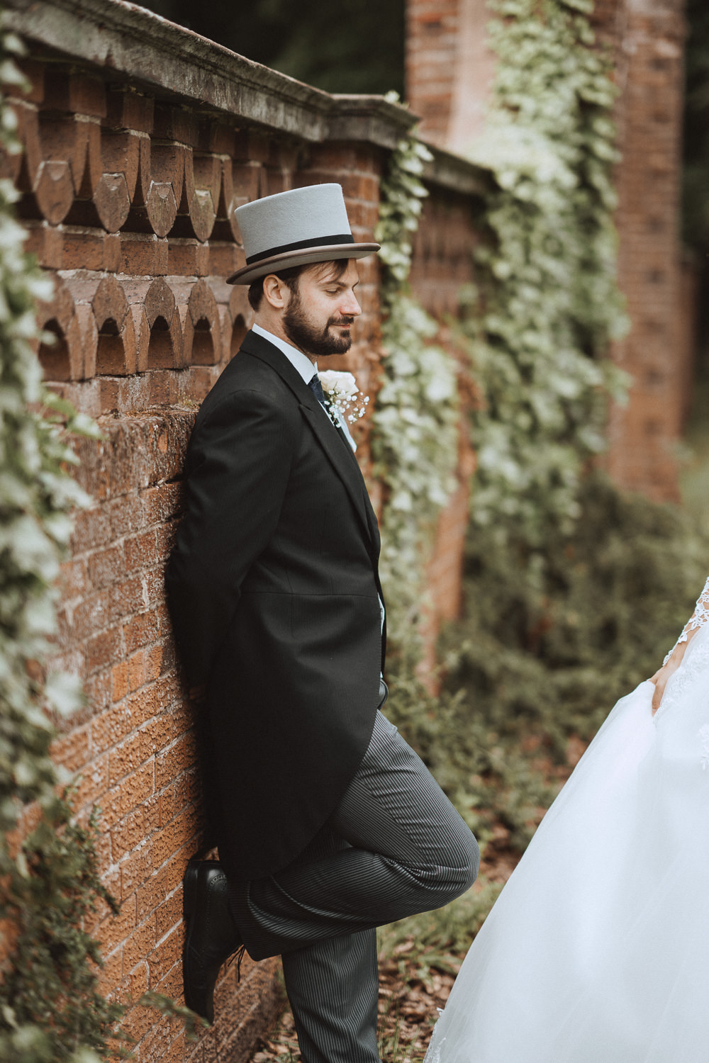 Groom leaning on the wall at Inglewood Manor, Cheshire