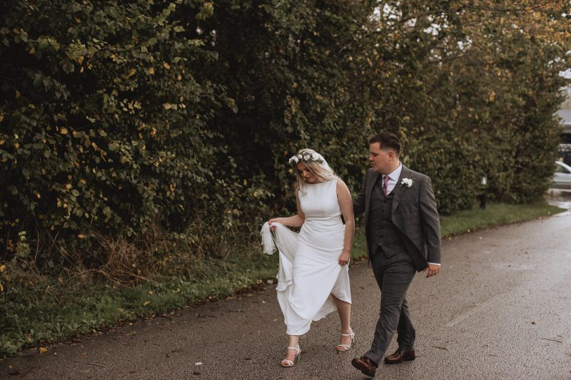 Bride and groom walking down the road at Faenol Fawn in Denbigh