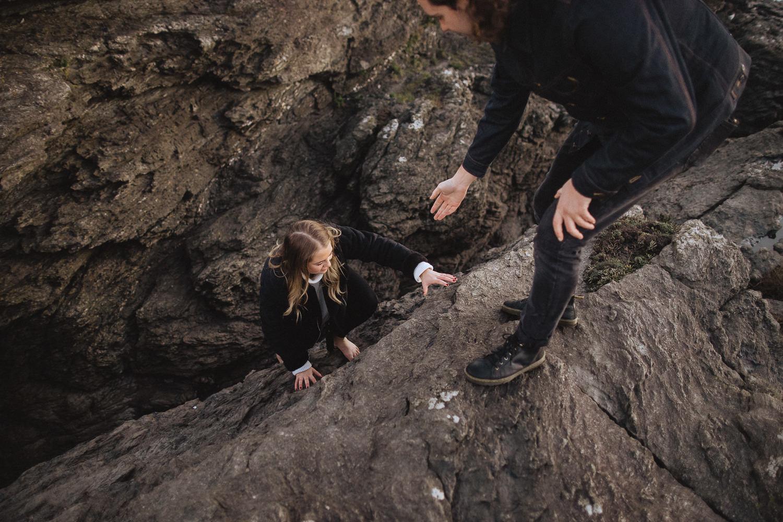 couple climbing rocks prewedding session at trearddur
